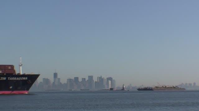 vídeos de stock e filmes b-roll de huge cargo ship through arthur kill channel to new york harbor, with lower manhattan in background. - salmini