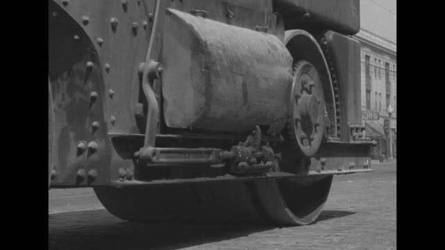 huge compactor machine on city street passes corner drug store cars on street // men with pickaxes dig at dirt next to barbed wire fence near country... - cement mixer stock videos and b-roll footage