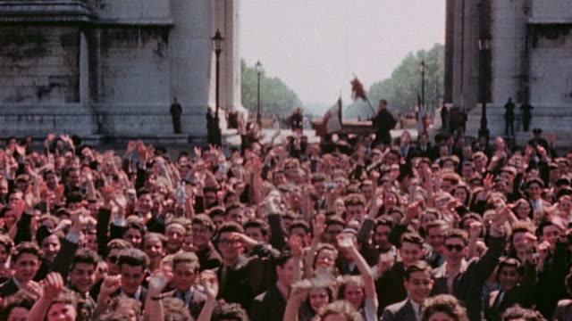 vídeos de stock, filmes e b-roll de huge crowd celebrating ve day at the arc de triomphe procession of allied flags bicyclist sitting on her bike smiling and parade of schoolchildren... - 1945