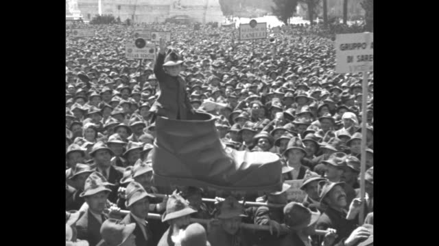 Huge crowd gathered in piazza in front of Victor Emmanuel Monument / young boy in mountaineer outfit stands in giant boot carried on poles by...