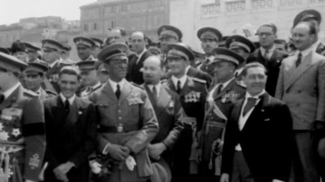 huge crowd gathered in the streets of rome to welcome famous aviators from around the world / cars containing famous pilots drive through the middle... - 1932 stock-videos und b-roll-filmmaterial