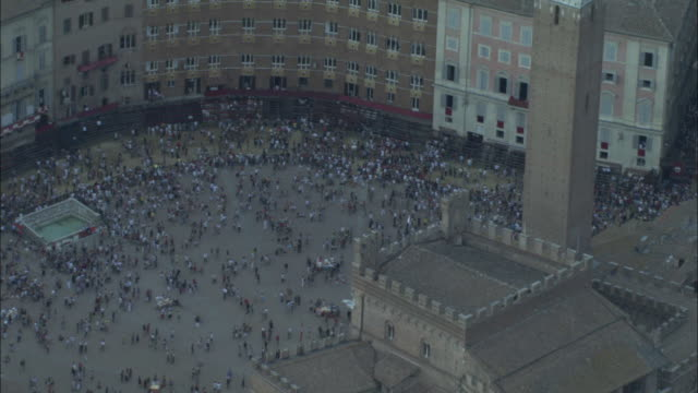 a huge crowd gathers in the piazza del campo in siena, italy. - campo stock videos & royalty-free footage