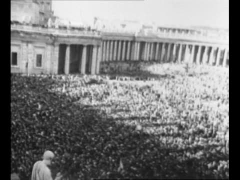 vidéos et rushes de huge crowd in st. peter's square, with statue of st. peter at left foreground, after liberation of rome during world war ii / tilt-up shot bell rings... - rome italy