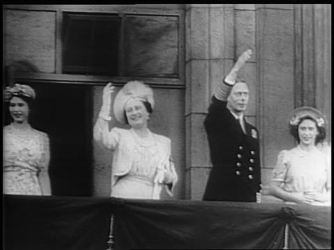 a huge crowd of britons at the buckingham palace gates to see king george vi the queen mother princess elizabeth and princess margaret on a balcony... - anno 1945 video stock e b–roll