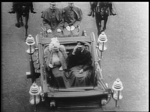 a huge crowd of britons rush the buckingham palace gates to see king george vi and the queen mother return in a carriage from the first day of... - the queen's speech state opening of uk parliament stock-videos und b-roll-filmmaterial