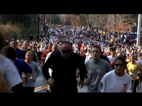huge crowd of runners head towards top of a hill from manchester road race running mass to top of hill on january 01 2012 - salmini stock videos and b-roll footage