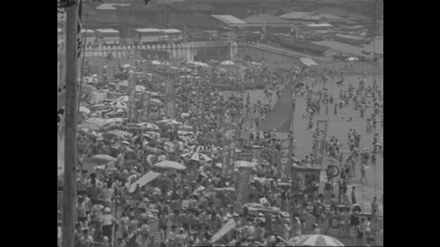 huge crowds amass at a beach near enoshima in kanagawa on a summer holiday in 1957. / during the high-growth period in japan. - 1950~1959年点の映像素材/bロール