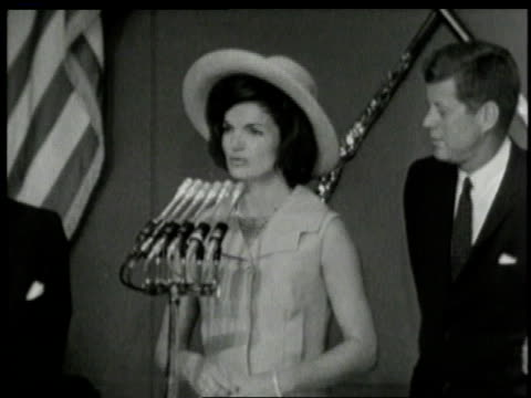huge crowds of people following reaching out their arms / jackie kennedy speaking at microphones with jfk standing beside her - cappello video stock e b–roll