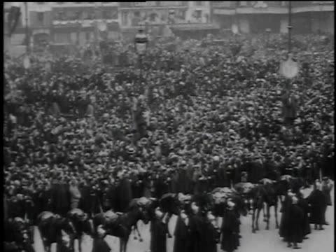 huge crowds of people gathering in square as president wilson and wife wave from window / paris france - anno 1918 video stock e b–roll