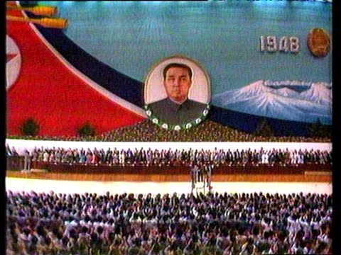 vídeos de stock e filmes b-roll de huge crowds stand cheering before large picture of north korean leader kim il sung pyongyang sep 88 - norte