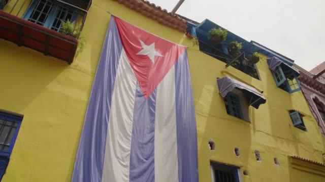vidéos et rushes de huge cuban flag on yellow building in havana, la habana (havana), cuba, west indies, caribbean, central america - cuba