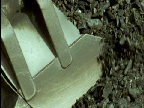 Huge digger bucket scoops up coal in coal mine UK