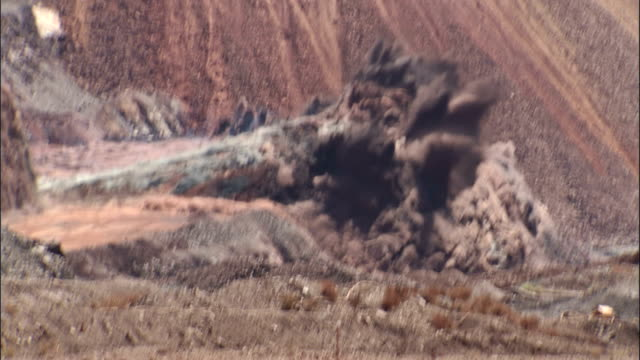 a huge explosion creates a dust cloud at a surface mine. available in hd. - bergbau stock-videos und b-roll-filmmaterial