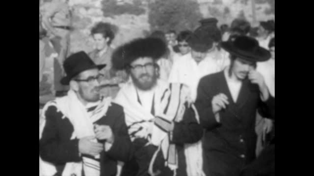 vidéos et rushes de huge line of orthodox jews walking to the wailing wall in jerusalem / everyone happy smiling and singing / packed crowd stand in front of wailing wall - 1967