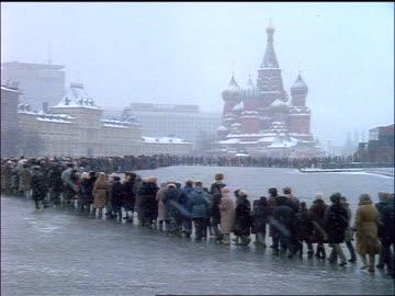pan huge line waiting to enter lenin's tomb in red square during snowstorm / moscow - tidigare sovjetunionen bildbanksvideor och videomaterial från bakom kulisserna