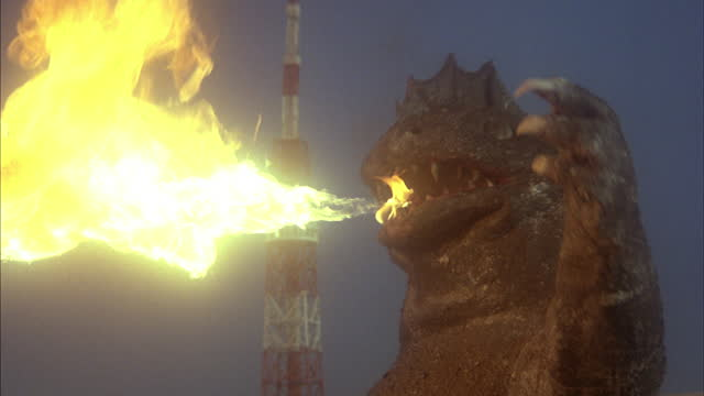 a huge monster exhales flames while standing in front of a tall radio tower. - large stock videos & royalty-free footage