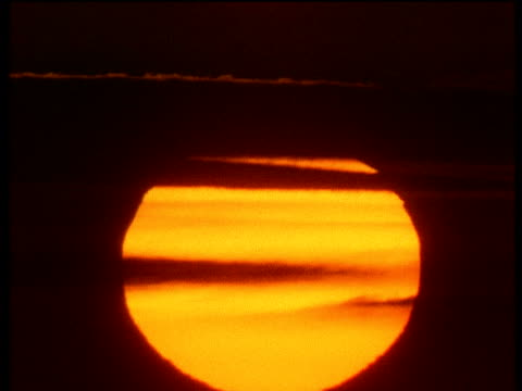 huge orange sunrise slowly lifting through misty dark clouds - good shape stock videos and b-roll footage