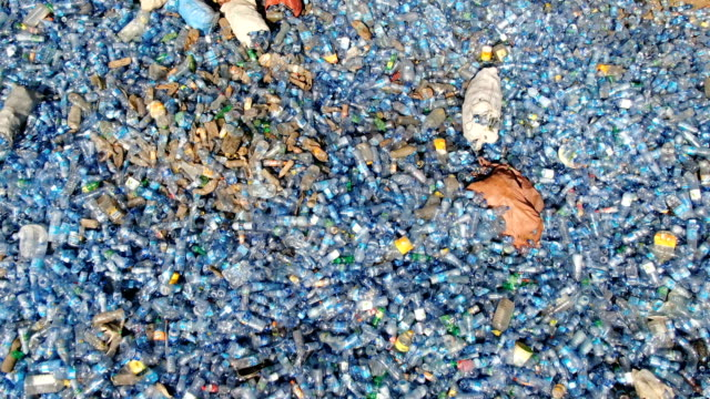huge piles of used blue mineral water plastic bottles waiting for  recycling / aerial drone shot - pollution stock videos & royalty-free footage