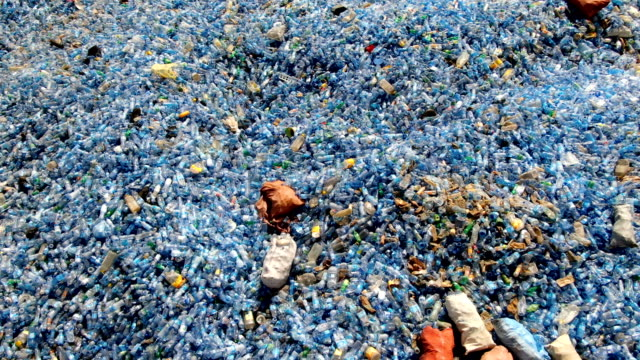 huge piles of used blue mineral water plastic bottles waiting for  recycling / aerial drone shot - horn of africa stock videos & royalty-free footage