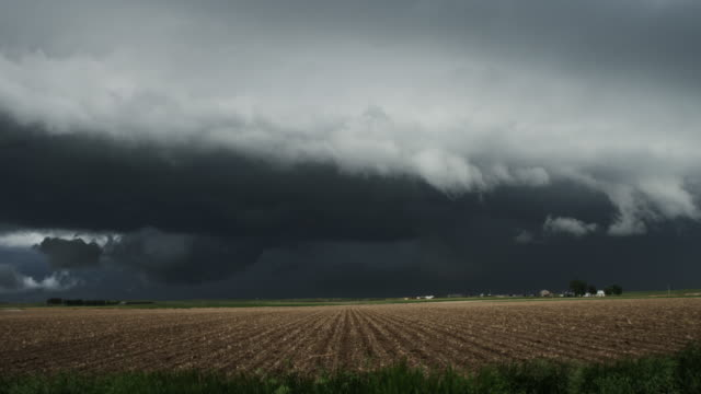Huge shelf cloud out ahead of a cool outflow of air from a thunderstorm above prairie cropland