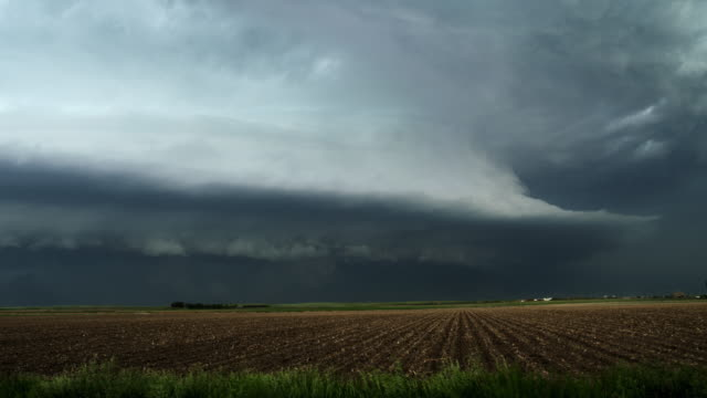 Huge shelf cloud out ahead of a cool outflow of air from a thunderstorm over cropland, time lapse