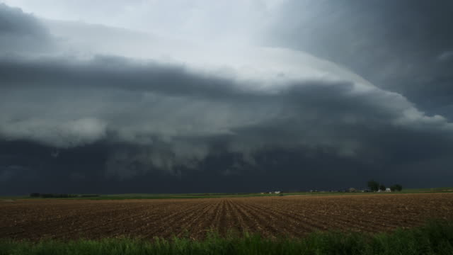Huge shelf cloud out ahead of a cool outflow of air from a thunderstorm over farmland, time lapse