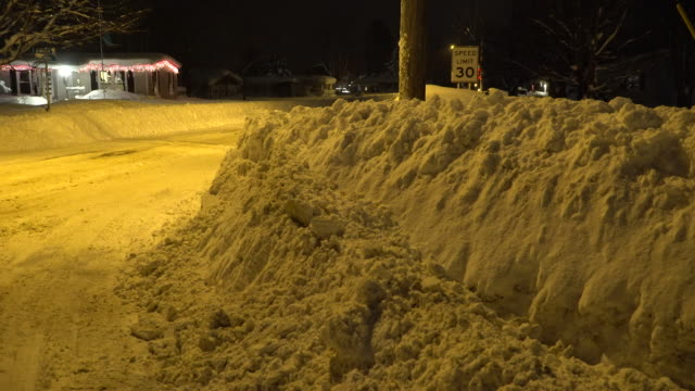 Huge snow mounds line a residential street in Upstate New York in the wake of record breaking lake effect snow fall that dumped between four and five...