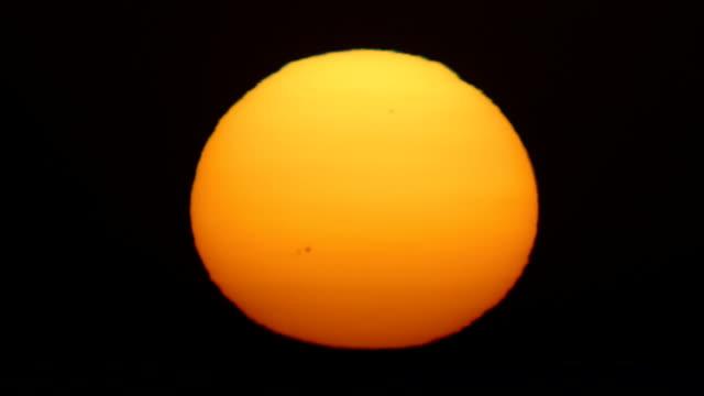 huge Sun rising and unveiling slowly above horizon, behind horizontal mountain ridge, with warm orange tones.