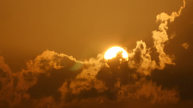 Huge sun rising with warm sunset colours and clouds
