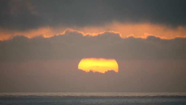 vidéos et rushes de huge sun setting in the sea with warm sunset colors - maroc
