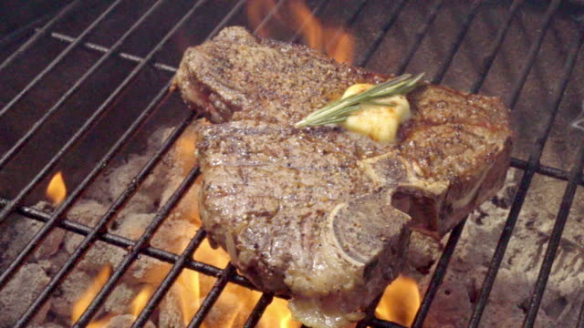 huge t-bone steak with grill marks on barbecue - steak stock videos & royalty-free footage