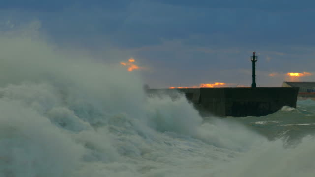 huge wave off the coast of the port at sunset - largo descrizione generale video stock e b–roll