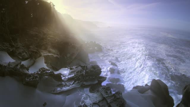 Huge waves crashing at dawn on rocky shore