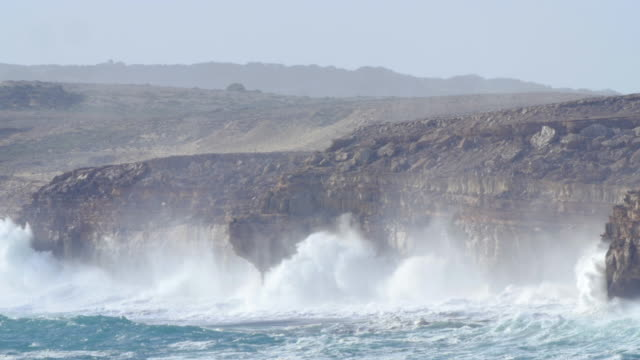 Huge waves explode against rugged cliffs