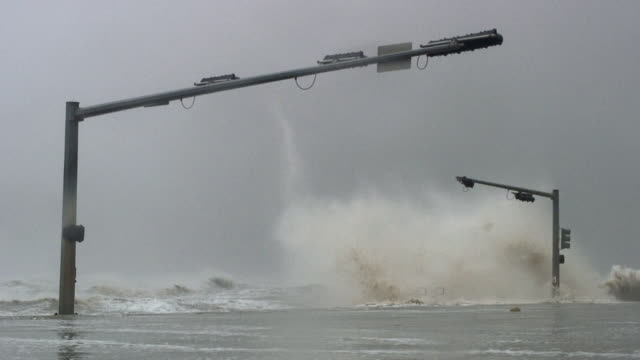 Huge waves striking seawall and traffic lights during hurricane.