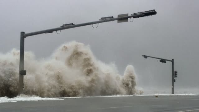 huge waves striking seawall and traffic lights during hurricane. - hurrikan stock-videos und b-roll-filmmaterial