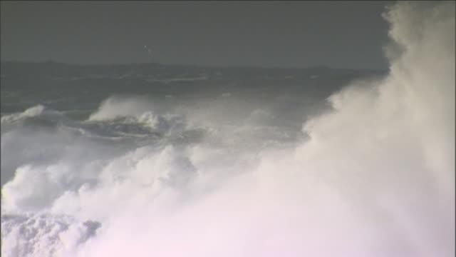 huge waves swell and crash over the ocean. - gezeiten stock-videos und b-roll-filmmaterial