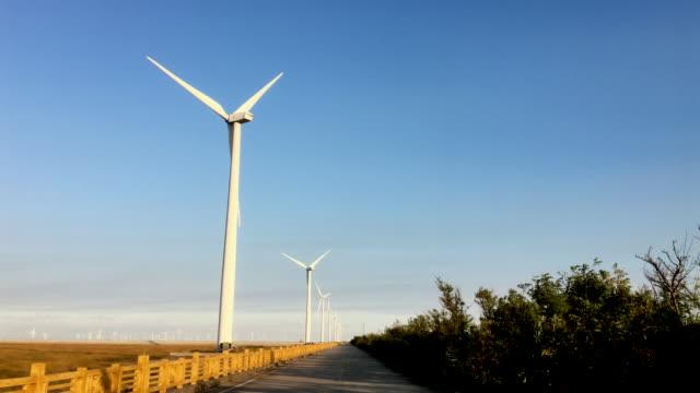 huge wind power turbine plant along coastal road