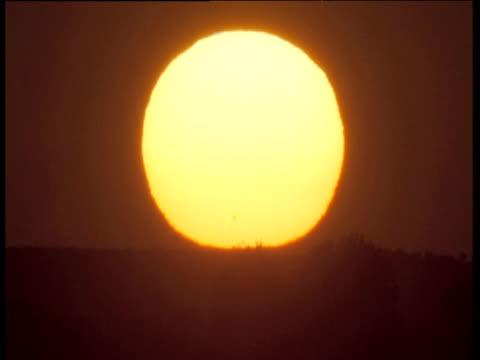 Huge yellow sunrise against dark sky