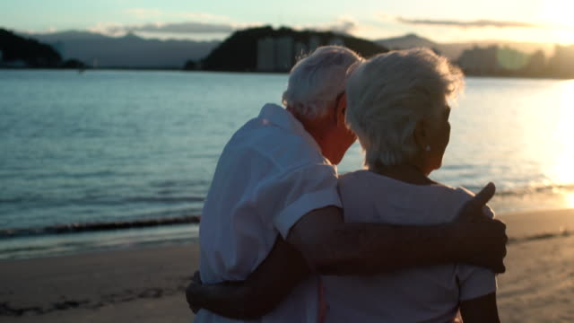 hugging elderly couple walking away from the camera with the old man singing , dancing and having fun at the sunset on the beach. - pensionierung stock-videos und b-roll-filmmaterial