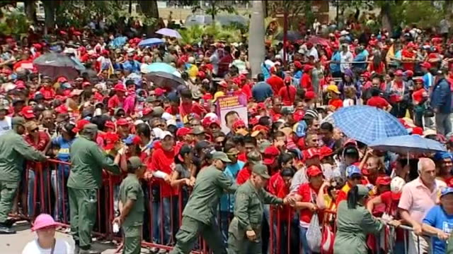 caracas ext mourners behind barriers chanting and punching air with fists as wait to see body of president hugo chavez lying in state sot mourners... - ウゴ・チャベス点の映像素材/bロール