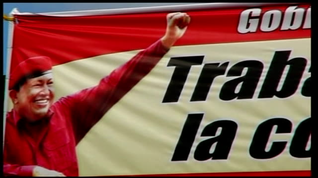 hugo chavez wins third term as president general view of ramshackle barrios with poster 'trabajando por la comunidad' hanging in the foreground close... - ウゴ・チャベス点の映像素材/bロール