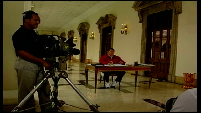 hugo chavez wins third term as president tx caracas int chavez seated at a table for weekly national address chavez speaking seated at a table tilt... - ウゴ・チャベス点の映像素材/bロール