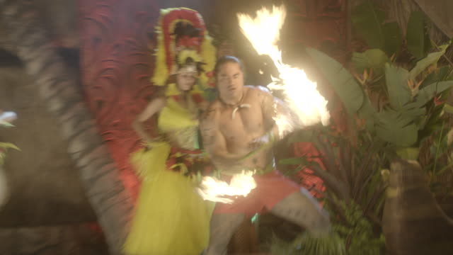 vídeos de stock, filmes e b-roll de hula dancers and torch throwers perform onstage during a luau in front of a fake volcano. - tocha tiki
