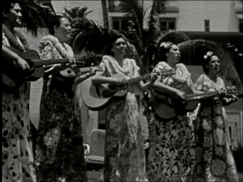 hula dancers hawaiian women strumming ukeleles women make floral wreath leis using flowers in a bowl / young woman kisses old man wearing many leis... - plucking an instrument stock videos and b-roll footage