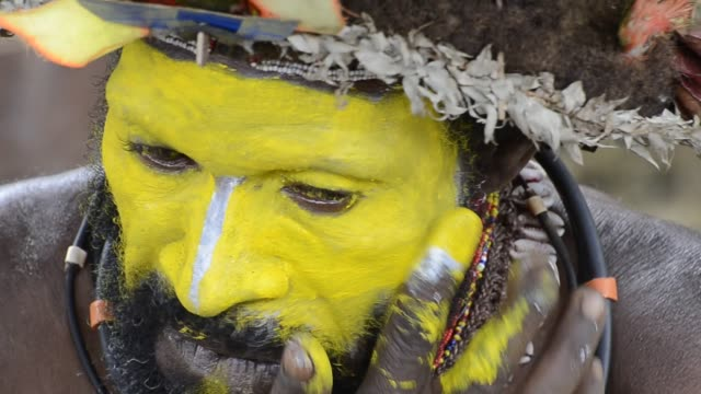 a huli wigman paints his face in preparation for a sing-sing dance. - minority groups stock videos & royalty-free footage