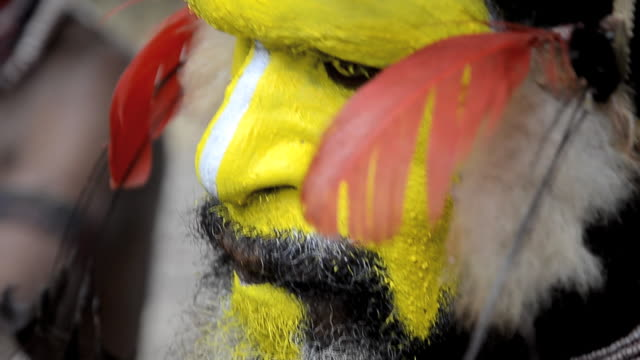 huli wigmen in papua new guinea paint their faces in preparation for a dance called a sing-sing. - minoranza video stock e b–roll