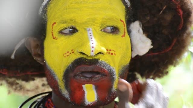 a huli wigmen wears facial paint as he prepares for a sing-sing dance. - minoranza video stock e b–roll