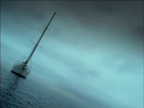 hull and bow of yacht with sails lowered floats on calm sea, south africa - tauwerk stock-videos und b-roll-filmmaterial