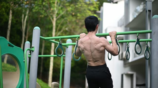 human back of asian chinese male athlete with naked upper body muscle doing workout at playground - human muscle stock videos & royalty-free footage